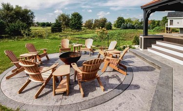 An expansive stamped concrete patio with a circular border that has several Adirondack chairs around it
