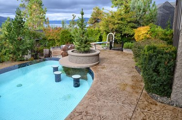 A brown concrete stamped patio with large cut squares and an in-ground swimming pool