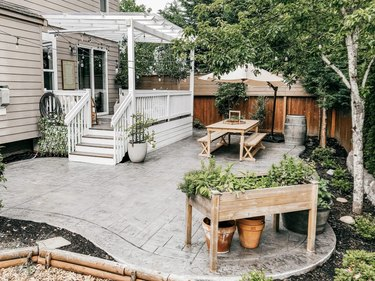 A light gray stamped concrete patio with a potting table and a picnic table