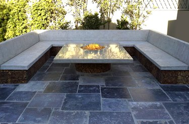 A modern gray square stamped concrete patio with a glass fire pit and a concrete bench