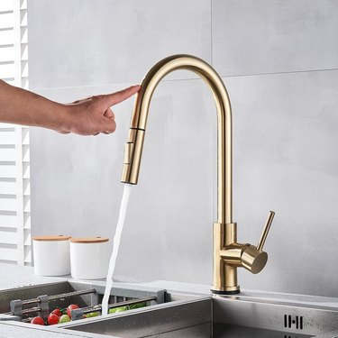 A person touching the brass kitchen faucet to turn it on