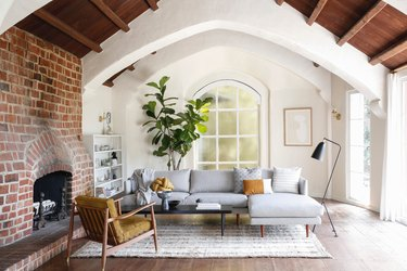 Minimalist living room with wood beam ceiling, red brick fireplace and large fiddle leaf fig.