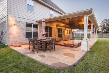 A multi-shade stamped concrete patio features a rounded corner