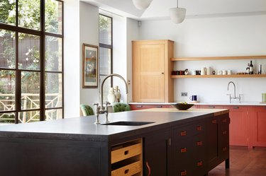 island with black kitchen cabinets and leather pulls