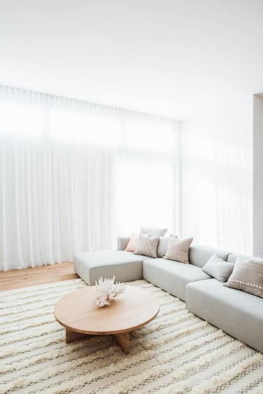 Bright and airy living room with sheer floor to ceiling curtains and a gray couch.