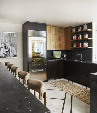 modern black kitchen with open shelving and gold cabinets