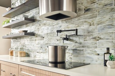 A black chrome pot-filler faucet in a kitchen with gray subway tiles and open shelving