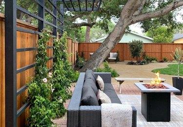 A black trellis with green plants is on a modern backyard patio