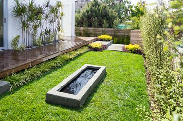 A small, modern water feature is in the middle of a lawn