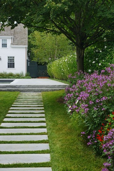 Horizontal concrete pavers are placed on a grassy path
