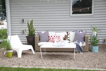 A pea gravel patio with white patio furniture and a multitude of plants
