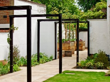 Rectangular and modern black arbors frame an entrance to a garden