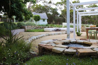 A classic English garden with a pea gravel patio has modern white arbors in it