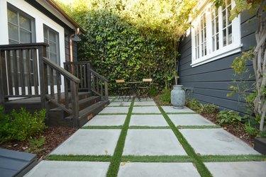 A black wood deck leads down to a concrete paver patio