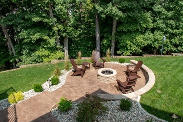 A circular stone patio is surrounded by a garden filled with white rocks