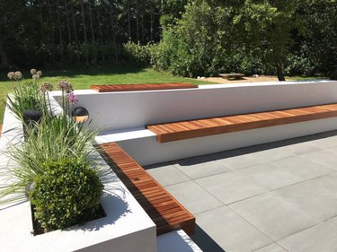 A  built-in concrete bench with wood adornment is on top of a concrete patio