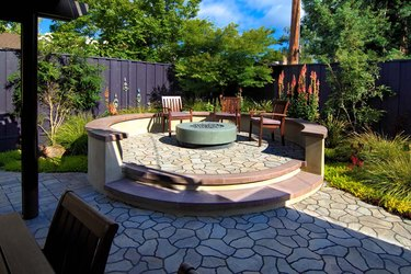 A raised circular stone patio features a fire pit