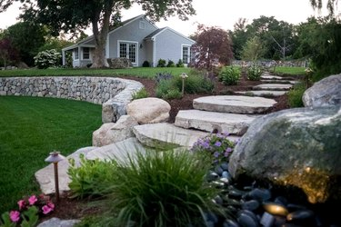 A sloped yard has large boulder stairs that lead down to a grassy path
