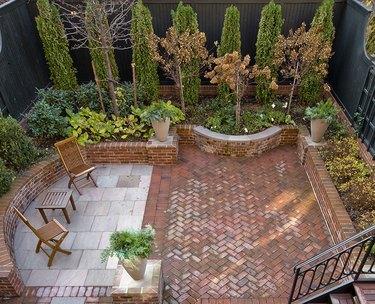 A patio has both brick herringbone and concrete pavers