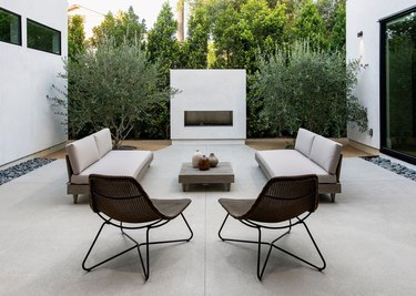 A white concrete outdoor fireplace is the centerpiece of this modern patio