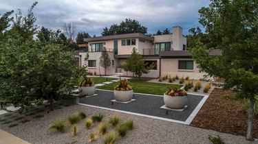 An aerial view of gravel patios with three large stone planters and a variety of plants