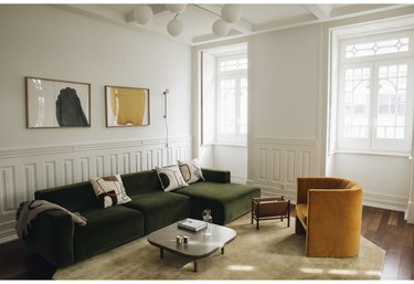 minimalist living room with green sofa and mustard lounge chair