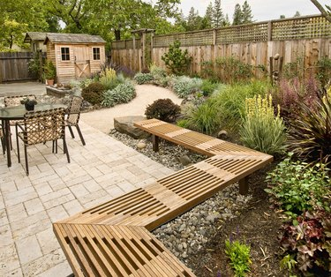 A decorative wooden bench frames a stamped concrete patio