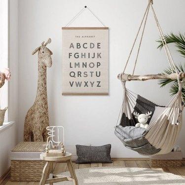 kids room with giraffe, hammock, and alphabet poster