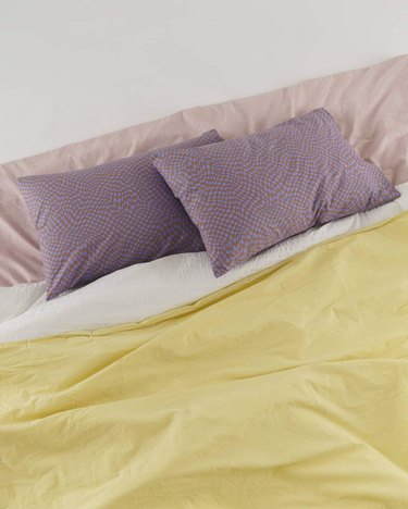 bed with two lavender pillows, pink, yellow, and white sheets