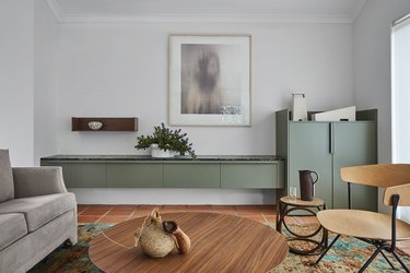 minimalist living room with green cabinets and terra cotta flooring