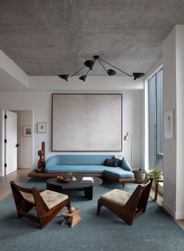 minimalist living room with white walls and concrete ceiling