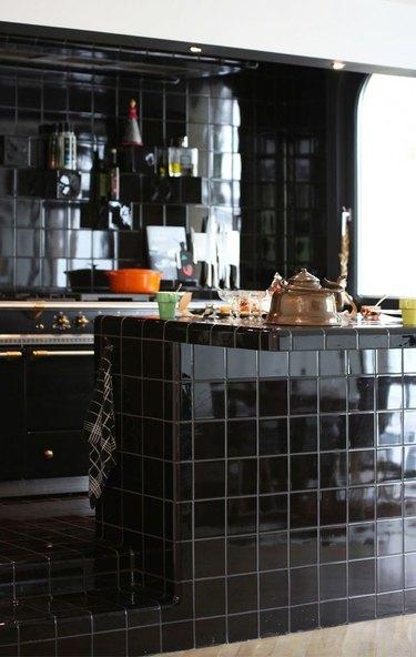 kitchen with black tile countertops, backsplash, and island back panel