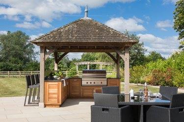 wooden outdoor kitchen under pergola