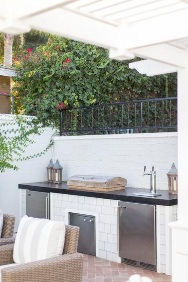 white brick and stainless steel outdoor kitchen with beer tap