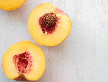 peaches with pits on white background