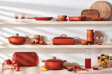 le creuset cayenne products on wood shelves
