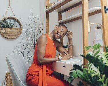 person wearing orange dress leaning against desk