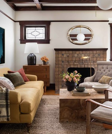 Living room with yellow couch, tile fireplace, lamps, coffee table, accent chairs, rug.