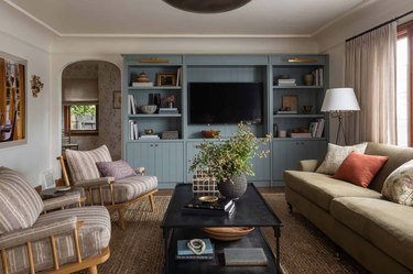 Living room with couch, chairs, coffee table, built in teal shelves.