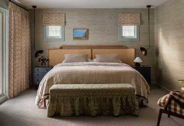 Bedroom with taupe bedding, walls, bench, curtains.