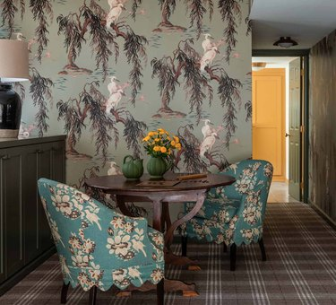 Living room with green patterned wallpaper, patterned chairs, checked rug.