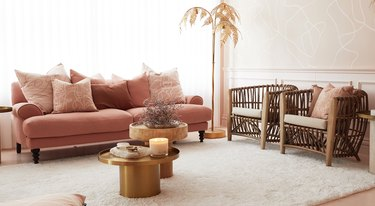 Living room with pink couch, cane accent chairs.