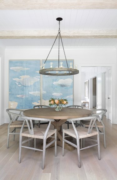Dining room with light gray dining set, floors, large blue art piece, chandelier.