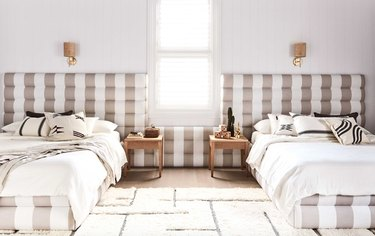 Bedroom with taupe patterned headboards, bedding, nightstands, sconces.