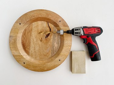 Drill through the holes with a drill, and sand any rough edges smooth.