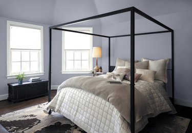 Bedroom with taupe bedding and lavender walls.