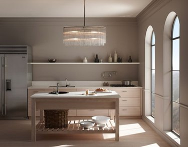 Taupe kitchen with island, stainless refrigerator, large chandelier.