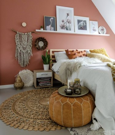 Bohemian bedroom with picture ledge shelf, macrame wall hanging, leather floor pouf, and burnt orange colored paint.