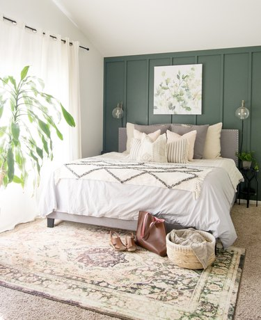 Minimalist bedroom with forest green accent wall and farmhouse bedding.