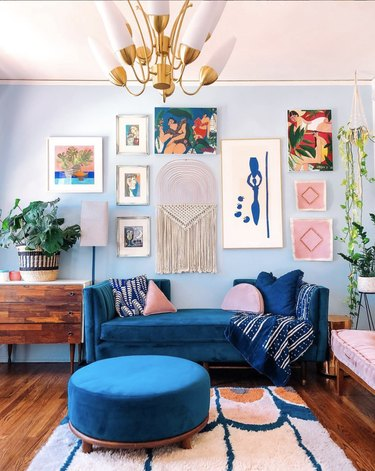 Eclectic living room with light blue accent wall, gallery artwork and bright blue sofa.